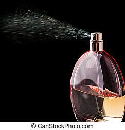 Bottle of perfume spraying over black