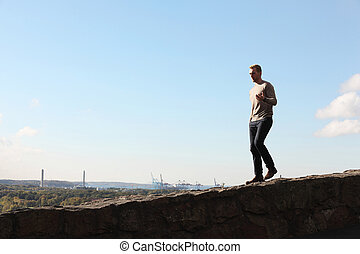 A man walking looking at the view - A lonely man wearing a...