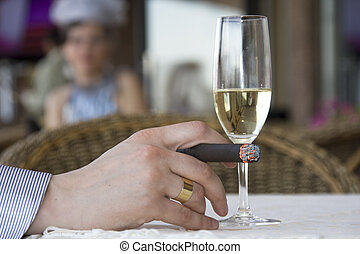 Man in cafe drinking wine and smoking cigar
