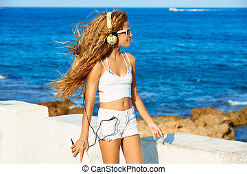 Blond kid teen girl headphones music on the beach