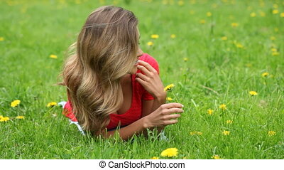Woman smell dandelion - Beautiful woman laying on grass and...