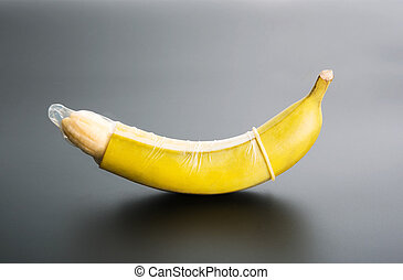 Banana with condom on grey background