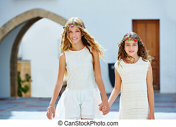 Kid girls walking hand in hand Mediterranean village - Kid...
