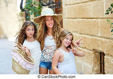 Tourist kid girls group in mediterranean white town