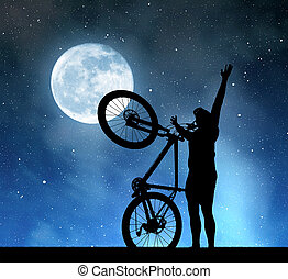 Silhouette of a man with a bicycle in the night sky with the...