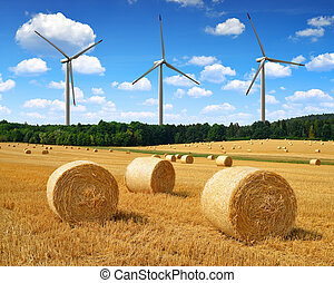 Straw bales on farmland on the background wind turbines