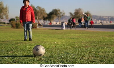 Young boy kicking ball in the grass outdoors
