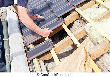 a roofer laying tile on the roof