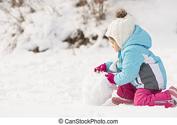 Child building snowman - Funny little girl in a warm winter...