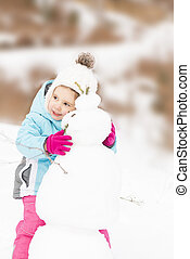 Little girl hugging a snowman - Funny little girl in a warm...