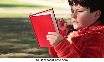 9 year old boy sitting on the grass reading a kids book