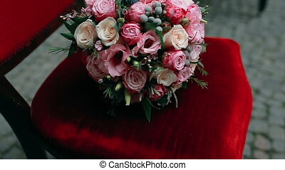 Wedding bouquet with roses on a red chair