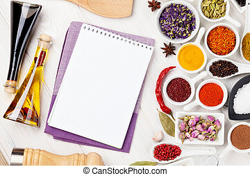 Various spices and condiments on white wooden background
