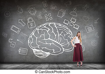 Woman stands beside big drawn brain on the gray wall
