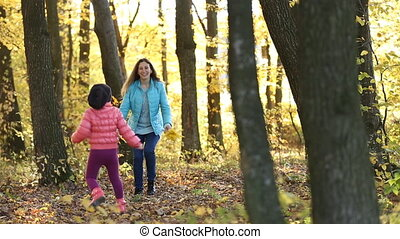 Mother with child walking in the autumn forest