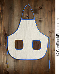 Blank apron with pockets on wooden background.