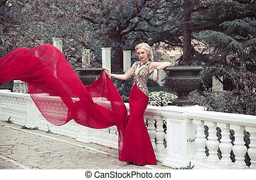 Beautiful elegant woman wearing in long mermaid fluttering fashion dress in winter park, outdoors full length portrait.