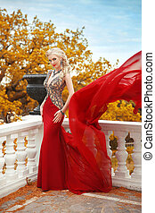 Sexy young beauty woman in fluttering red dress. Elegant slim lady posing on the balcony with baluster over autumn park view.