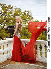 Young beautiful caucasian woman in gorgeous red dress with waving flying fabric, fashion female posing on the balcony with park view.