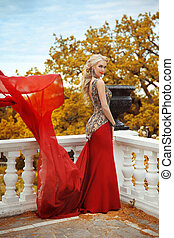 Beautiful gorgeous Woman model in elegant mermaid red dress with blowing on the balcony in autumn park. Blond lady with wedding curly hair style  in long gown.