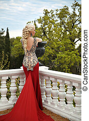 Beautiful sexy Woman with elegant hair style in mermaid red dress on the balcony enjoying park view. Blond lady in long gown.