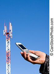 Phone and GSM station - Cellular telephone in a hand against...