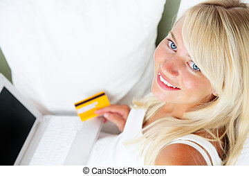 Online Shopping - Young smiling woman sitting with laptop...