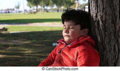 Portrait of cute boy sleeping near tree in park