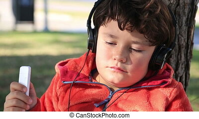 Young boy listening to music - Happy cute schoolboy in park...