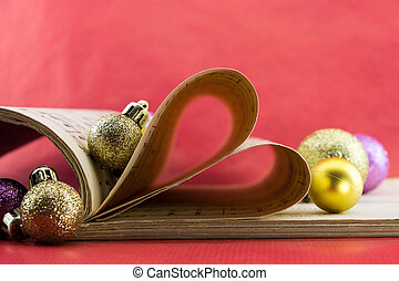 Music notation book with pages shaping heart and Christmas...