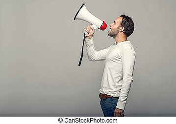 Man speaking over a megaphone as he makes a public address,...