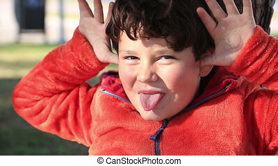 Young boy making funny faces - Happy schoolboy making funny...