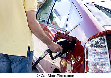 Filling the tank of a car - Closeup of male hand topping up...