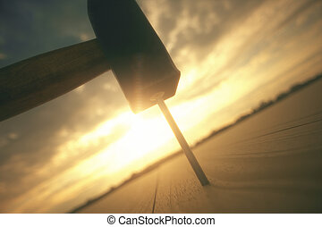 Close-up Of Hammer Hitting On Nail With Dramatic Sky
