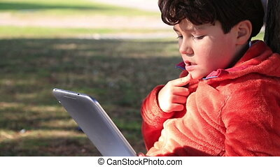 Boy using digital tablet outdoor - Young happy boy using...