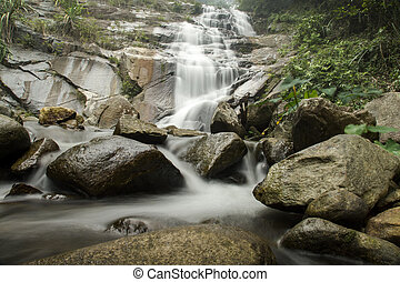 Waterfall and stone in the rain-forest at Tone Pliw...