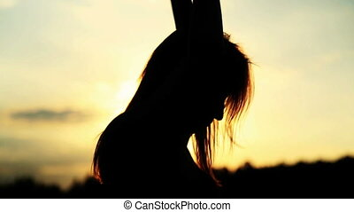 Silhouette of the woman dancing during beautiful sunset...