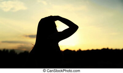 Silhouette of the woman dancing during beautiful sunset....