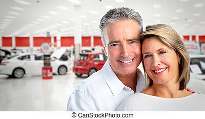 Happy senior couple near new car.