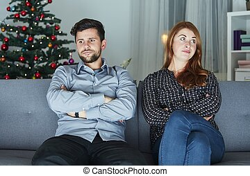 young modern couple is irritated of christmas with christmas...