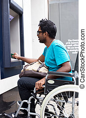 wheelchair atm - disabled man withdrawing cash at the atm