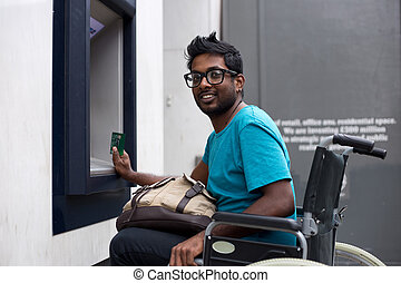 wheelchair atm - disabled man at the cash machine