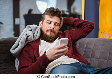 Relaxed young man lying on sofa and using cellphone -...