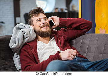 Smiling happy boy lying and talking on mobile phone -...