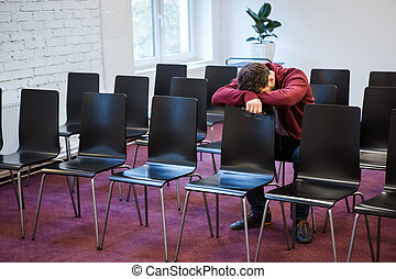 Tired young man snoozed in conference room