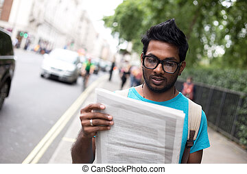 reading news - indian man in the street reading a newspaper