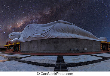 White reclining buddha under starry night with clearly milky...