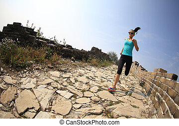 woman runner athlete running on trail at chinese great wall...