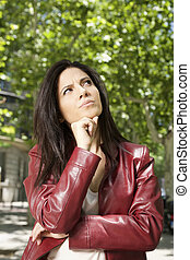 pensive woman - pretty brunette woman with red leather...