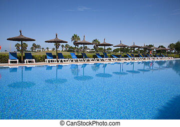 pool side with hammocks and umbrellas - swimming pool side...